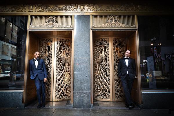 wedding portrait grooms in tuxedos by gold doors ornate art deco peacock design motif