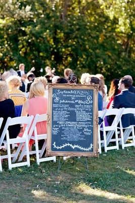 Wedding ceremony program on a chalkboard with ornate wood frame
