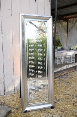 Silver mirrored table number display at barn wedding