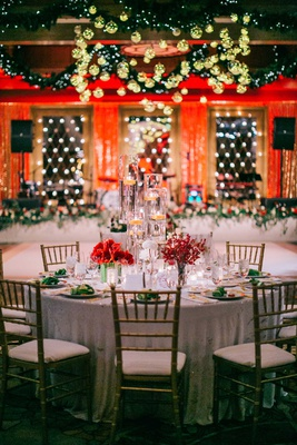 white linen gold chairs red flowers tall floating candles gold ornaments green garland dance floor