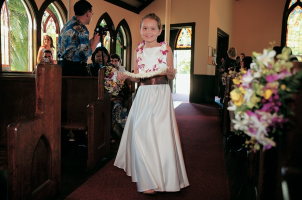 flower girl wearing white long dress and pink lei