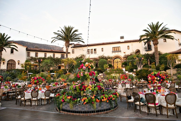 outdoor wedding reception colorful flowers spanish fountain with greenery and pink orange flowers