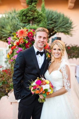 newlyweds posing colorful vibrant bouquet la jolla wedding veil tuxedo la valenica hotel cute couple