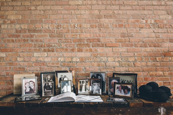Wedding ceremony rustic brick wall with family photos in frames and guest book on table