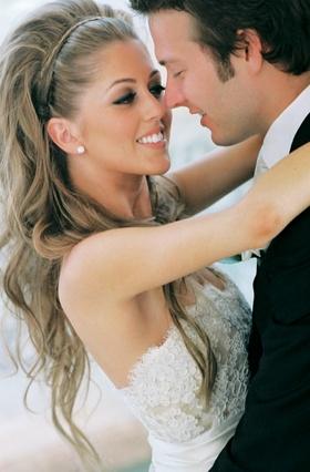 Bride hugs groom with long blonde hair and nice makeup