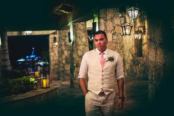 a groom in a dark hallway poses in a tan suit with pink tie and green boutonniere