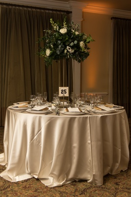 champagne linens, gold stand with heavy greenery centerpiece, table numbers from baseball players