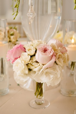 pink roses and white flowers surround base of glass centerpiece vase