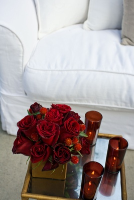 Red rose centerpiece with candles on gold table