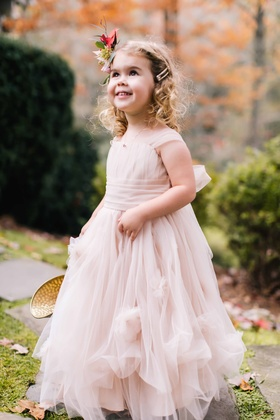 adorable flower girl in flowing pink princess dress with ribbon sash and floral headband