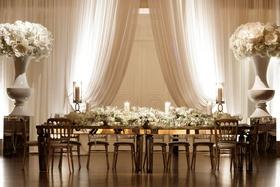 Wedding reception head table white drapery urn oversized flower decor long white flower runner