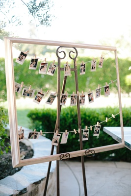 polaroid photos for guest book hung up in frame by miniature clothespins