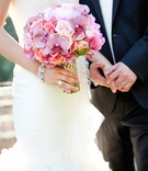 Bride in a sleeveless Vera Wang dress with bouquet of pink & light purple orchids, roses, peonies