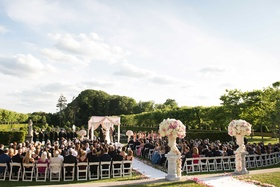 Wedding ceremony at Oheka Castle with white and pink flower arrangements, pink rose petals aisle