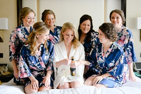 bride opening champagne bottle on bed with bridesmaids in matching flower print silk robes