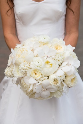 Bride holding bouquet with orchids, ranunculus, peonies, and additional white blooms