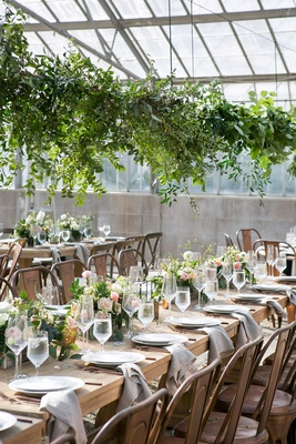 wedding reception wood table industrial chairs low centerpiece overhead greenery greenhouse venue