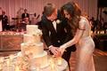 Bride in Inbal Dror wedding dress and groom in tuxedo cutting four layer ivory wedding cake flowers