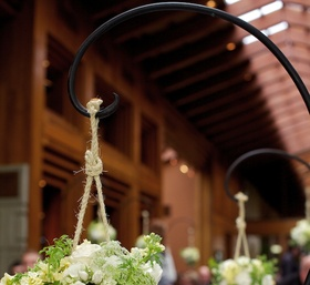 Shepherd hook holding white flowers hanging from rope