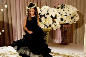 Flower girl in a sleeveless black dress with a white floral halo