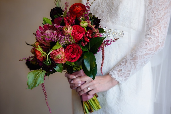 Bride wearing long-sleeve lace dress holding bright flowers