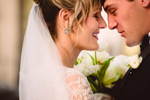 bride in monique lhuillier, groom touch foreheads during first look