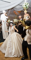 Bride and groom in Venice style masks with stilt performers