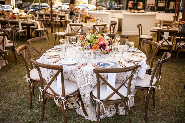 wood charis with white cushions, textured ivory linen, vibrant low centerpiece, rose gold flatware