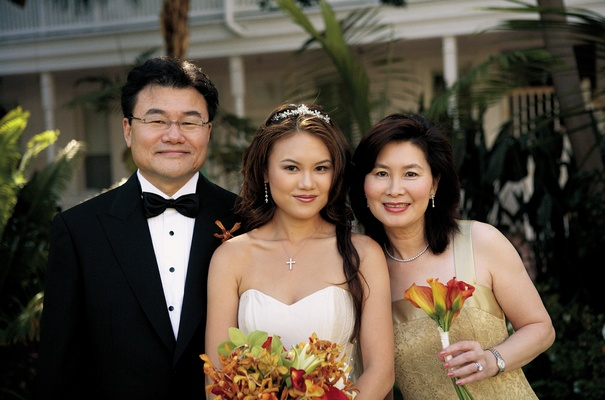 parents and bride holding orange bouquet