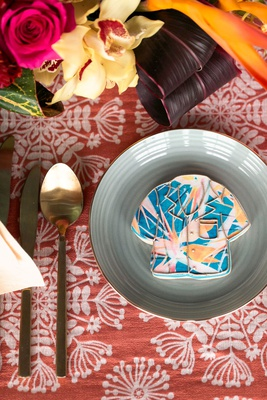 wedding styled shoot gold flatware blue plate gold rim blue pink orange yellow hawaiian shirt