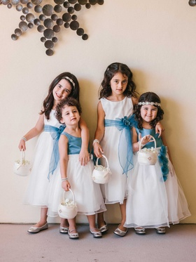 Four flower girls carrying baskets with white dresses and blue sashes or bodices headbands