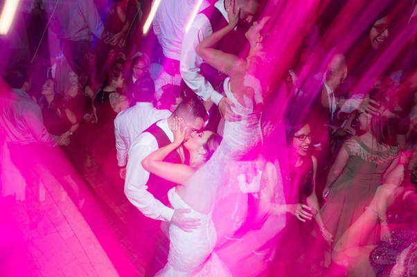 couple kiss on dance floor party filter pink blue rave feeling having fun california wedding recepti