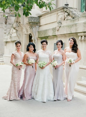 bridesmaids in mismatched blush, grey, cream dresses holding small nosegays of garden roses