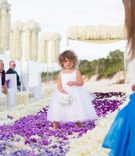 Flower girl in white dress walks down flower petal sand aisle
