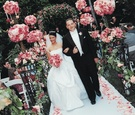 Couple walks up aisle surrounded by pink flowers