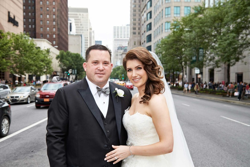 bride and groom embrace in chicago on a busy street
