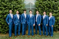 wedding party groom and groomsmen in bright blue suits with pink ties hedge wall charlotte summer