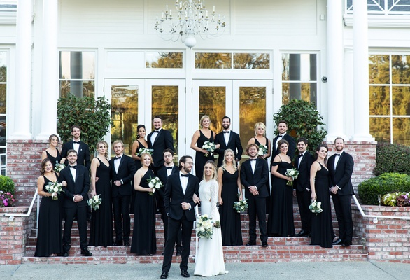 bride in sarah seven dress, groom and groomsmen in tux, bridesmaids in black show me your mumu dress