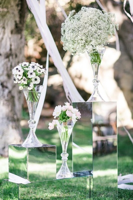 White anemones with blue centers, pink and ivory tulips, baby's breath in glass vases at outdoor alt