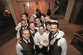 Groom in white shirt and tie surrounded by groomsmen with white shirts and brown vests
