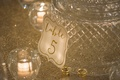 White reception table card with gold lettering against cut crystal by votive candle