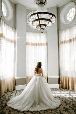 bride in tara keely wedding dress ball gown in room with tall windows chandelier sunny sunlit