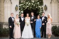 wedding portrait groom with family and bride mother of bride in blue dress long sleeves church arch