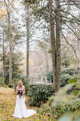 bride with wine colored floral bouquet and white dress stands in field and forest setting