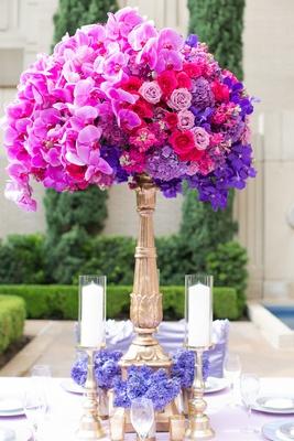 Wedding reception centerpiece of magenta orchids, light purple, hot pink roses, purple hydrangeas
