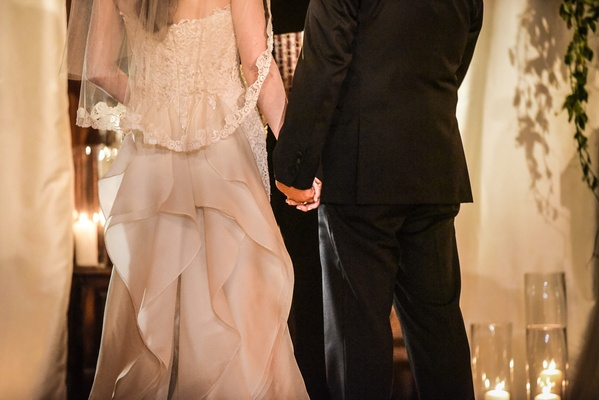 bride in oscar de la renta, groom in tommy hilfiger hold hands during ceremony