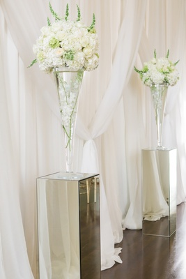 Mirrored pillars with white floral arrangements at front of ceremony space