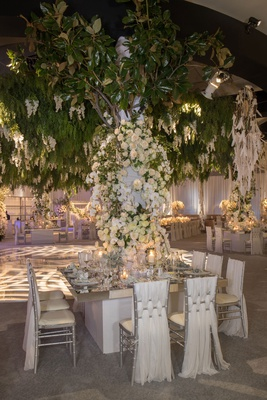 wedding reception ballroom square mirror tablee draped chairs white flowers greenery over chandelier