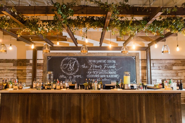 whiskey bar with greenery lights and chalkboard wooden bar