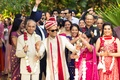Indian groom in ivory, gold, and red outfit and turban enters ceremony with his procession